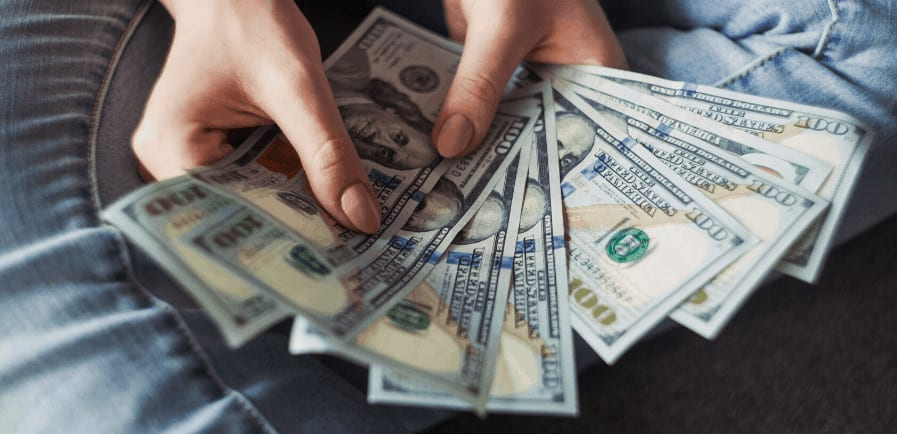 hands holding 100 dollars