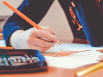 person writing with an orange colored pencil