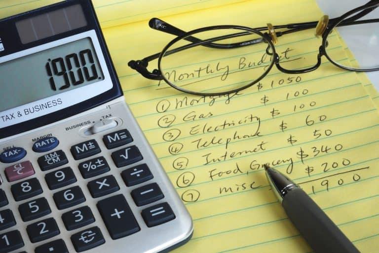 budgeting with a calculator and yellow notepad